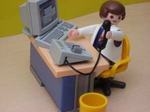Playmobil man sat at desk.